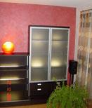 Gestaltung mit Lesando Lehmputz farbig gewachst, Laminatboden.  Wohnzimmerwand mit Metallic-Lasur im kräftigen Rotton beschichtet.