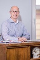 Dr. Thorsten Radam am Schreibtisch