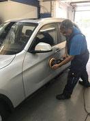 Mitarbeiter von Wash Clean Bochum beim Polieren der Autotüren im Rahmen der Autoaufbereitung