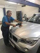Mitarbeiter von Wash Clean Bochum beim Polieren der Motorhaube im Rahmen der Autoaufbereitung