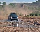4 x 4 Offroader fährt durch ein Wadi, Hintergrund Kasbah, Marokko