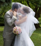 A picture of a Bride & Groom kissing with the brides veil over them both.