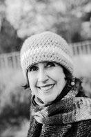 Frau in mittleren Jahren mit kurzen schwarzen Haaren und dunklen Augen