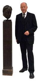 Direktor Dr. Willi Urbanek steht neben einer Büste von Erich Fried.