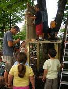 Ein Vater baut mit den Kinder ein Baumhaus
