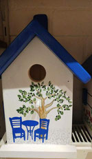 Grieks huisje met bistrootje en olijfboom
