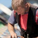 Dachdecker führt Schweißarbeiten auf einem Dach aus