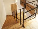 木製ストリップ階段に黒いアイアン手すり