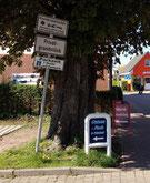 Das Hinweisschild steht versteckt unter einem Baum an der Einfahrt zum Parkplatz. Ein vorbeifahrender Autofahrer kann es leicht übersehen.