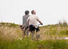 Ein Paar fährt Rad auf einem Weg an grasbewachsenen Dünen der Ostsee entlang