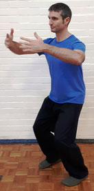 Classical Chinese Martial Arts Practitioner demonstrating a standing meditation posture called 'Holding The Ball'