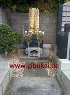 """Frontansicht des Funakoshi-Grabs. Rechts steht der Stein mit der """"Grabinschrift""""."""