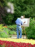 Malen mitten in der Natur. Maler steht mit Staffelei zwischen Blumen.