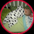 Baby mit Babyschlafsack liegend