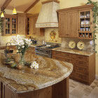 A warm, traditional kitchen with granite countertops and a custom mural in the travertine backsplash