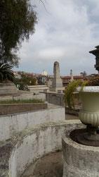 Un pot de fleur en béton et des monuments funéraires en béton du cimetière de Valparaiso avec une vue sur une partie de la colline d'en face