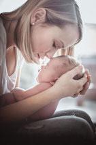 Kopf an Kopf Foto von Newborn Baby auf dem Schoss der Mutter fotografiert von der Schweizer Familien Fotografin Monkeyjolie