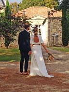 Les mariés vus de dos devant l'entrée de la cour du Château La Hitte, vignoble AOC Buzet en Nouvelle Aquitaine