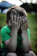 enfant qui souffre en se cachant le visage
