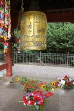 Blumen liegen am 6.August im Tempel der Weltfriedensglocke Berlin. Foto: Helga Karl