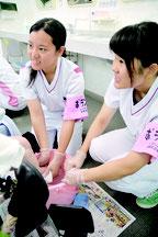 ふれあい看護体験で、患者の足を洗う高校生=21日午前、かりゆし病院