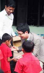 バングラディシュの小学生に「ミドリムシ入りクッキー」を配布する出雲氏=バングラディシュ、ダッカ
