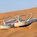 weiße Flipflops im goldgelbem Sand