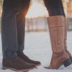Füße in Stiefeln von einem Mann und einer Frau, die sich im Schnee gegenüberstehen, der Hintergrund ist unscharf
