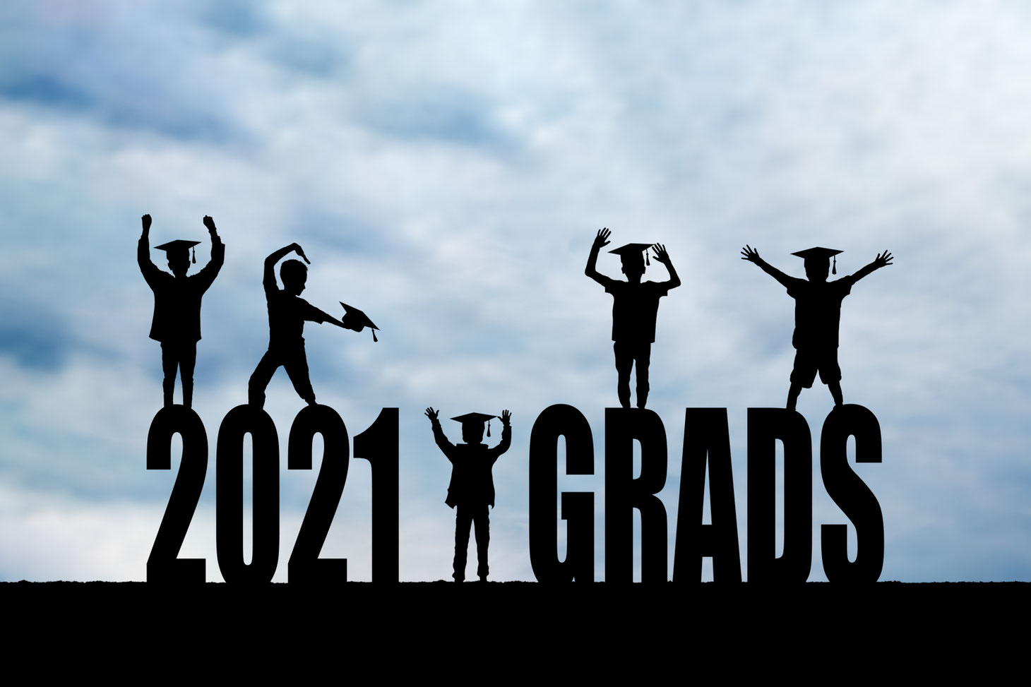 5 boys in silhouette wearing grad caps on block letters reading 2021 grads. The sky is blue