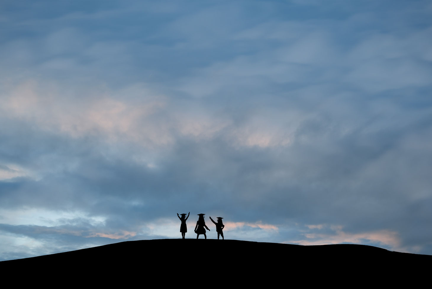 silhouettes of 3 girls in grad caps on a hill against a blue sky with bits of pink