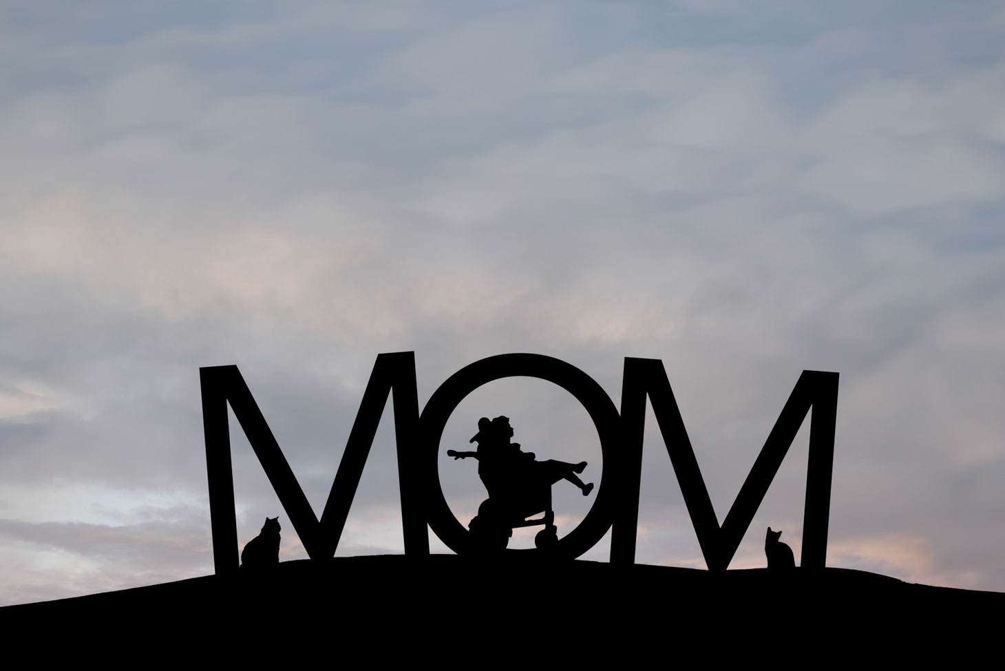 silhouettes of girl in a wheelchair and 2 cats in the letters MOM on a hill. Sky is blue, grey, and pink.