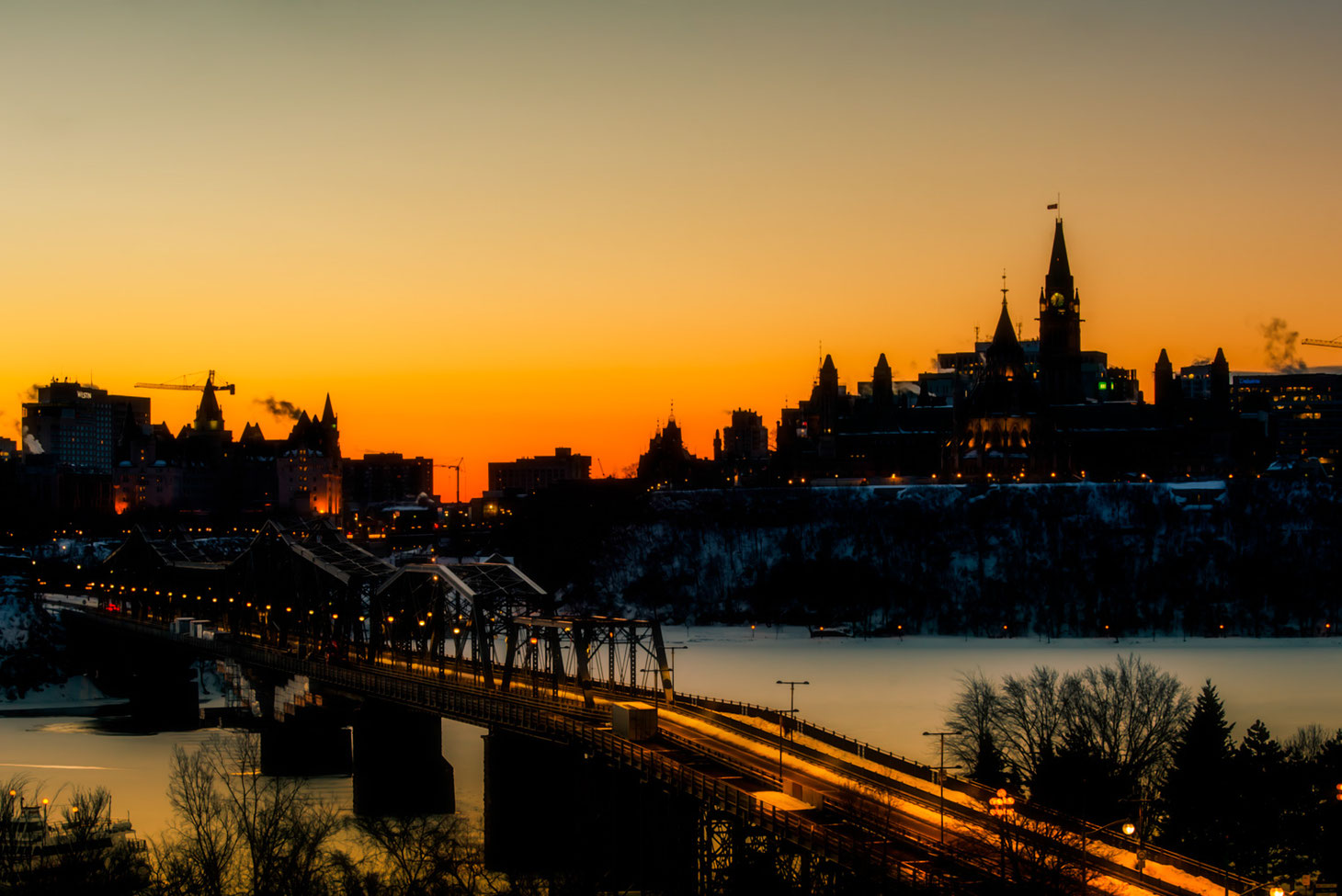 Photo of Ottawa parliament taken at sunrise from Gatineau Quebec. Chateau Laurier and bridge between Ontario and Quebec are also visible. River under bridge is frozen.