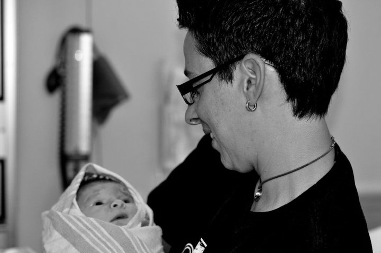 Black and white photo of a new mom holding her baby wrapped in a blanket.