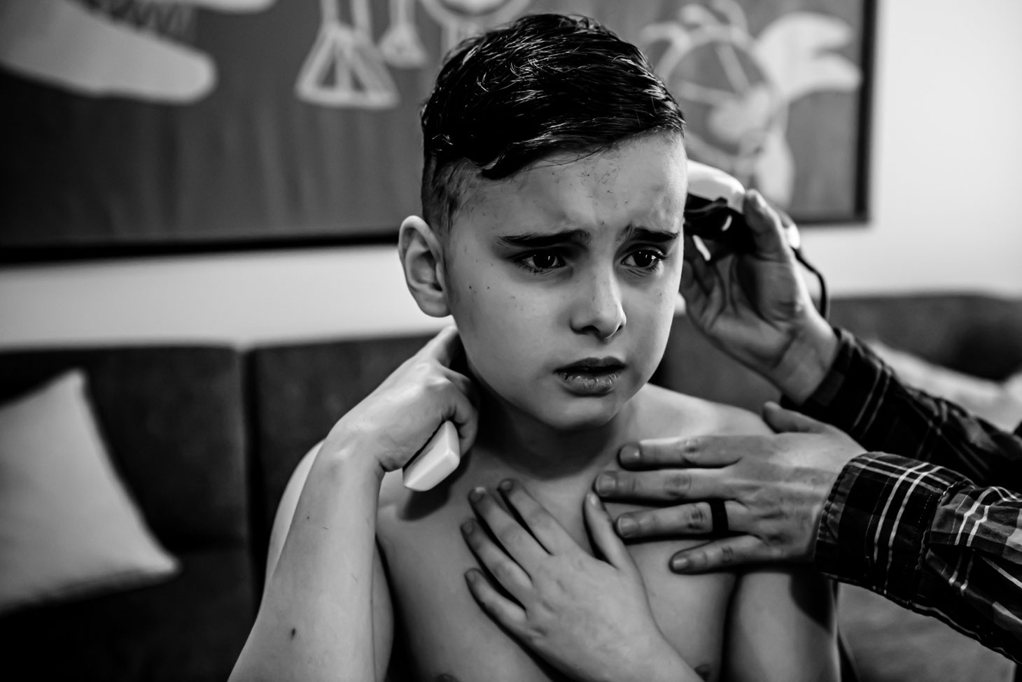 Black and white photo of mom giving child a haircut. Son looks unhappy.