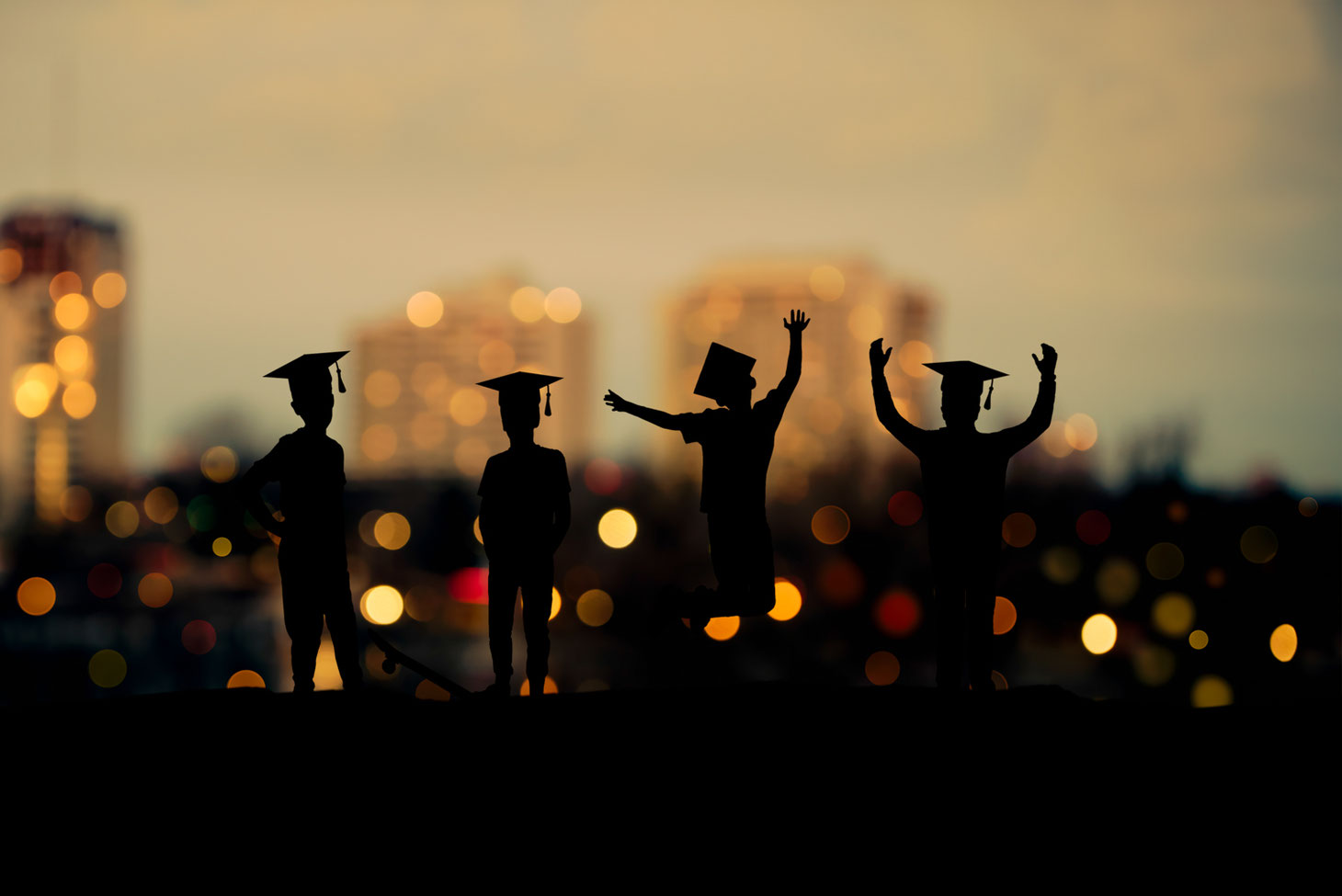 silhouettes of 4 boys in grad caps in front of a city view at sunset.