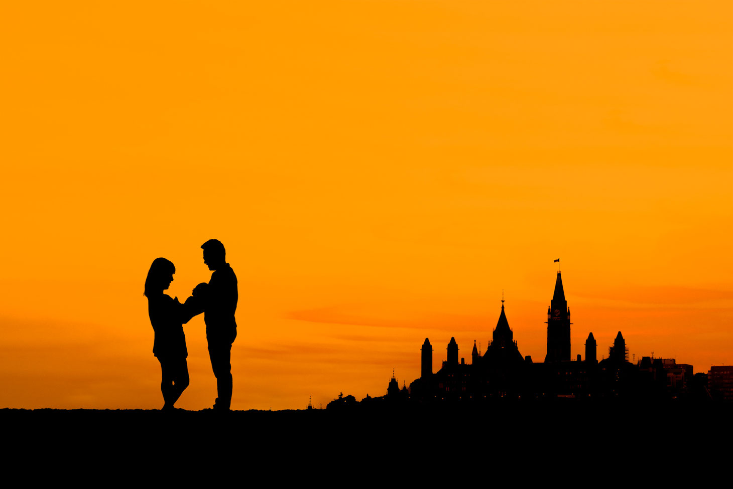 silhouette of mother, new baby, and father next to a silhouette of parliament hill in Ottawa Ontario. Sky is orange with a small amount of clouds.