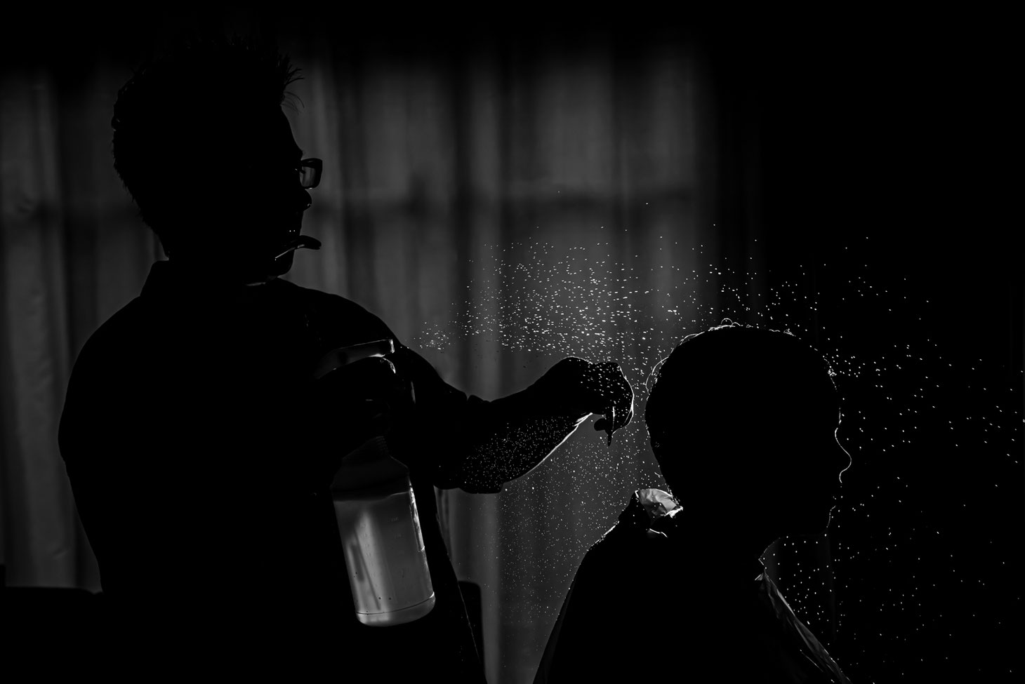 Black and white photo of mom giving child a haircut. Photo is backlit with child and mom in shadow and water droplets visible