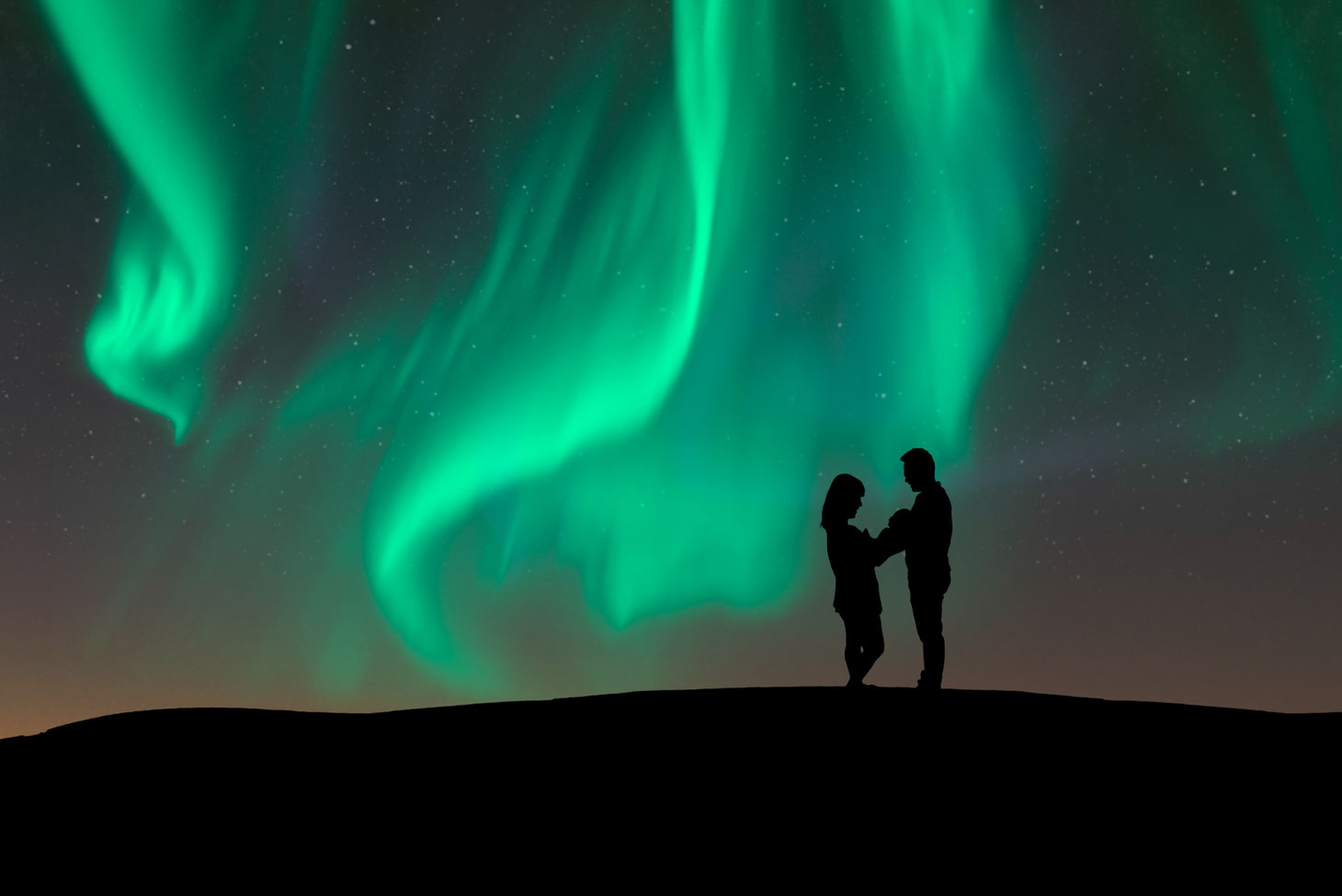 silhouette of mother, new baby, and father on a hill. Sky shows the green Northern Lights and stars. Sky is dark blue with some pink and yellow.