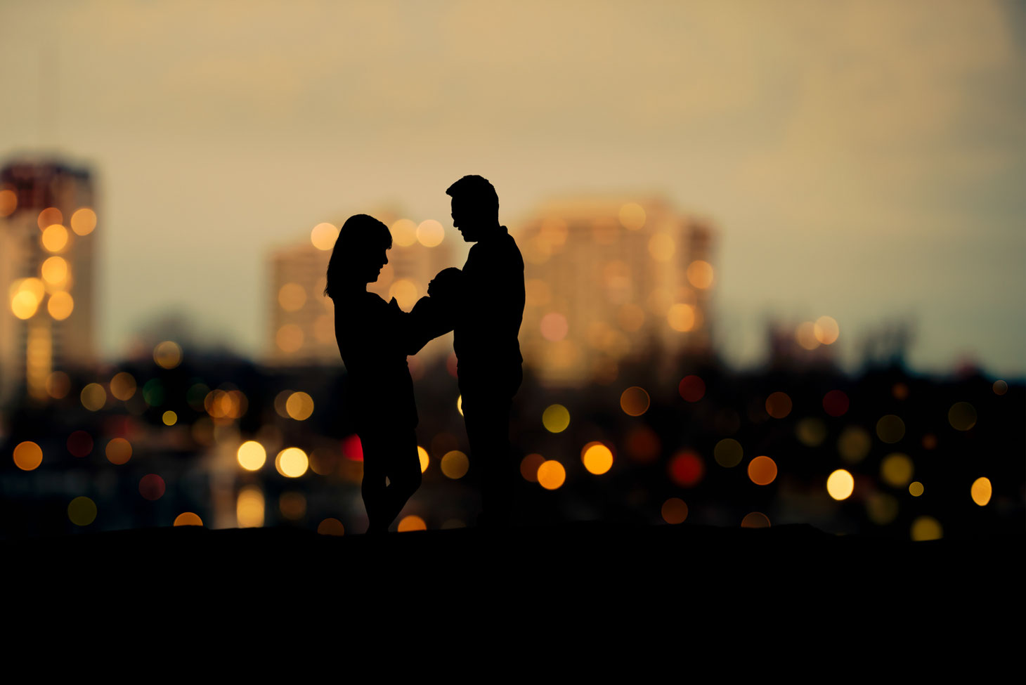 silhouette of mother, new baby, and father against bokeh city view at sunrise.