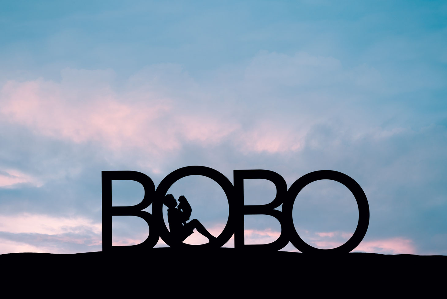 silhouette of boy and dog in the first O in the word BOBO. Sky is pink and blue.