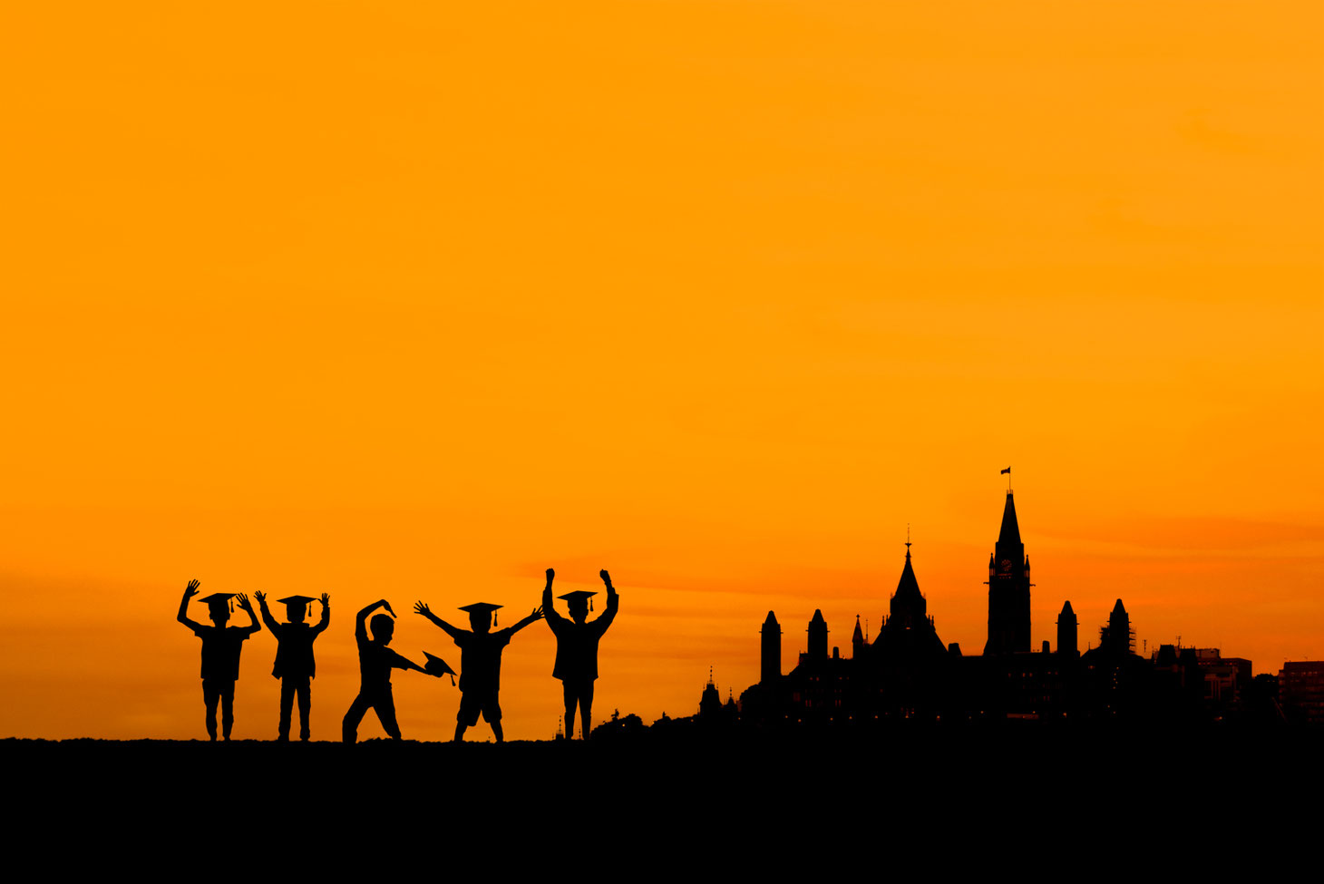 5 boys in silhouette in front of an orange sky next to a silhouette of parliament hill in Ottawa Ontario