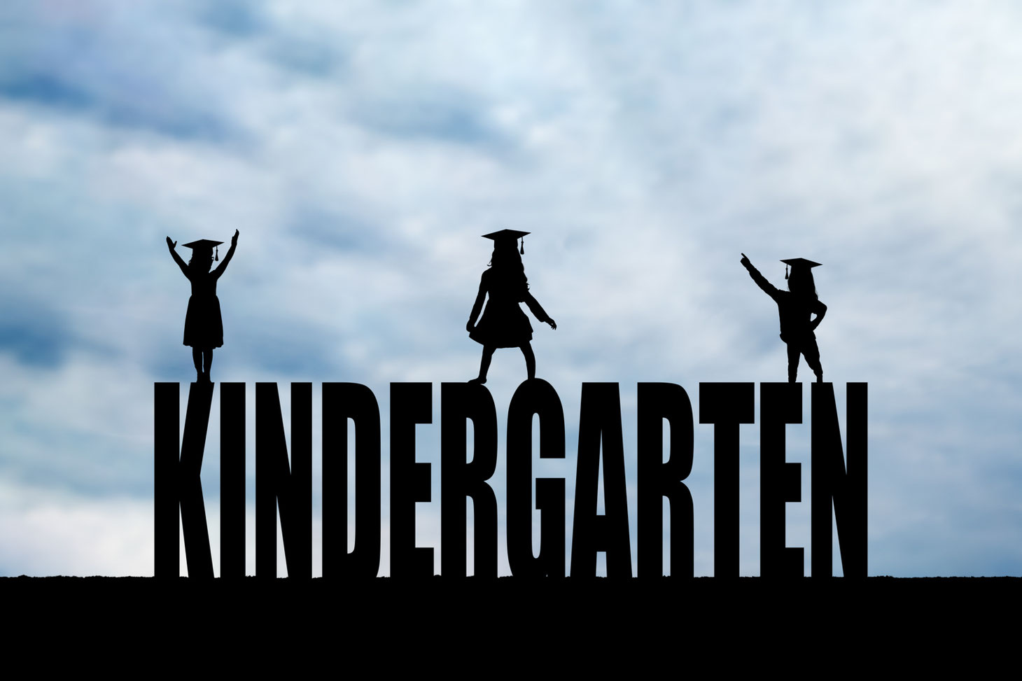 silhouettes of 3 girls with grad caps in front of a blue sky on top of the letters KINDERGARTEN
