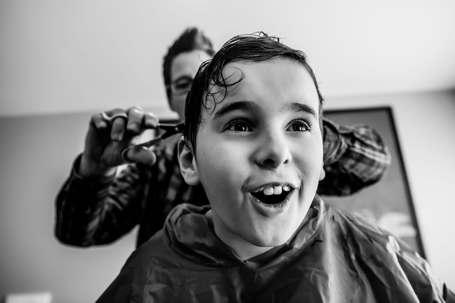Black and white photo of mom giving child a haircut.