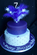 2 tier purple and white birthday cake with diamante ribbon and purple feathers