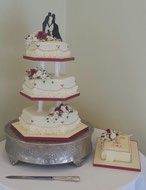 3 tier  hexagonal wedding cake wiith red and ivory flowers and matching bible cake