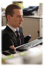 Das Bild entstand während meines Praktikums 2013. Ich sitze mit Anzug und Krawatte vor dem PC und arbeite fleißig.