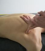 Abgebildet ist die manuelle Kompression auf dem Schulterblatt bei der Triggerpunkt-Therapie.