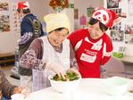 シンボルとなる「赤いエプロン」姿でボランティアに参加する従業員