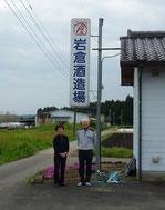 写真は、蔵の看板前で撮った岩倉夫妻です。廻りは畑だらけです。いつも二人三脚。