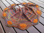 Autumn-toned shawl with orange cartwheel features around the edge